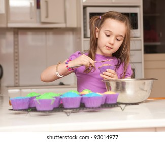A six year old girl baking cupcakes in their kitchen at home