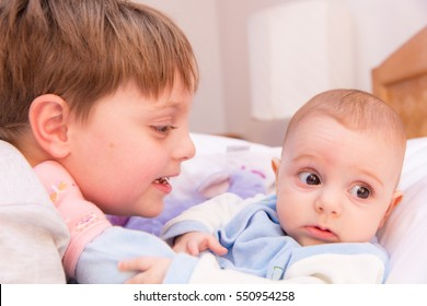 Six year old toddler sharing tender and affectionate moments with his six month old baby sister.