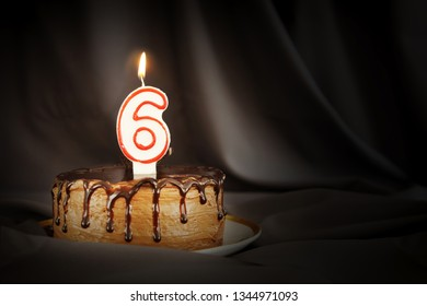 Six years anniversary. Birthday chocolate cake with white burning candle in the form of number Six. Dark background with black cloth