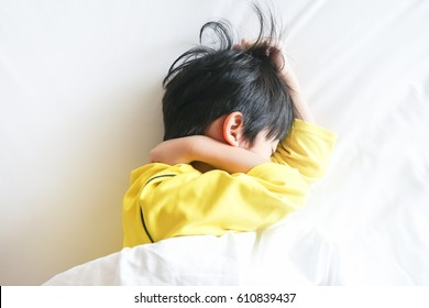 Six years old Asian child sleeping on white bedsheet in bed