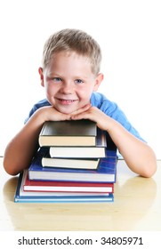 Six years old boy sitting at the table with a pile of books. Isolated on white.