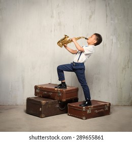 six years old boy stand on old suitcases and play sax. instagram toned