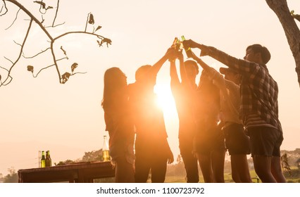 Six young entrepreneur gathering together toast for success in business start up, group party at dusk