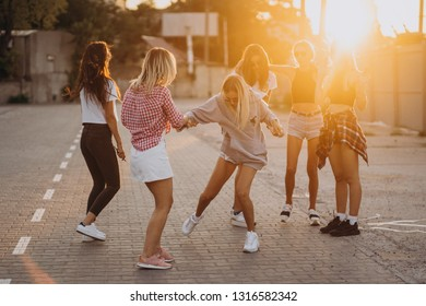 Six young women dance in a car park