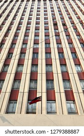 Sixteen story modern building in cream and garnet colors-symmetrical rows of windows-Philippine flag waving-corner of Jorge Bocobo Street and Teodoro M.Kalaw Avenue-Ermita Barangay. Manila-Philippines