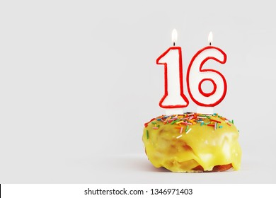 Sixteen  years anniversary. Birthday cupcake with white burning candles with red border in the form of number Sixteen. Light gray background with copy space