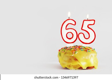 Sixty five years anniversary. Birthday cupcake with white burning candles with red border in the form of 65 number. Light gray background with copy space