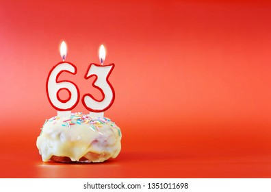 Sixty three years birthday. Cupcake with white burning candle in the form of number 63. Vivid red background with copy space