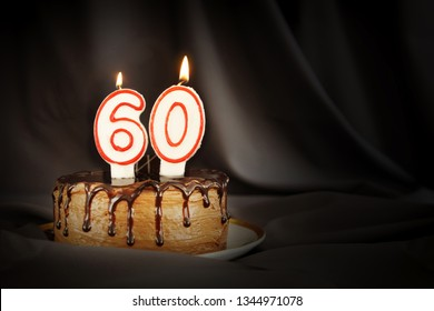 Sixty years anniversary. Birthday chocolate cake with white burning candles in the form of number Sixty. Dark background with black cloth
