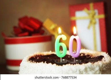 Sixty years birthday. Cake with burning candles and gifts