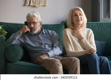 Sixty years old couple aged spouses sitting on couch resting at home, elderly wife soap opera lover and annoyed fed-up husband watching melodrama, different tastes free time weekend activities concept