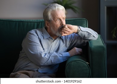 Sixty years old mature man sitting alone on couch at home thinking lost on sad thoughts, pondering about personal or health problems and midlife crisis, senior widower male feels lonely concept image