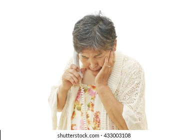 Sixty years old woman to a conversation on the phone ; trouble, worry, shock