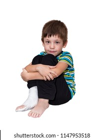 The six-year-old boy sits with the broken leg in plaster. Isolated on the white.