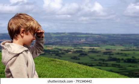 A six-year-old boy standing on the hill smiling and looking forward