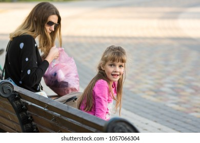 Six-year-old girl and mother sat on a bench for a walk, the girl joyfully looked at the frame