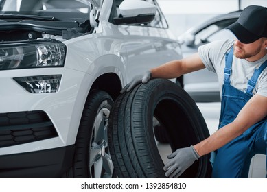 Size comparison. Mechanic holding a tire at the repair garage. Replacement of winter and summer tires.