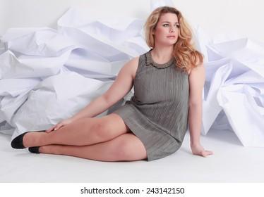 Größe Ganzes Porträt einer schönen, gut geschwungenen jungen blonden Frau, die auf Weiß in grauem Kleid und Pumpen posiert / Porträt einer schönen, mehr geschwungenen jungen blonden Frau