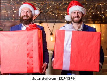 Size matters. Biggest gift for christmas. Big wrapped box with ribbon. Great surprise. Prepare huge surprise gift. Men compete who has larger size. Bigger gift battle. Men santa carry big gift boxes.