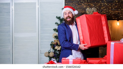 Size matters. Biggest gift for christmas. Celebrate christmas with giant gifts. Big wrapped box with ribbon. Great surprise. Prepare huge surprise gift. Man santa claus hat carry big gift box.