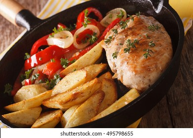 Sizling Lunch: chicken breast with roasted potatoes and vegetables close-up on a frying pan. horizontal