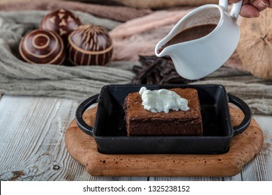 sizzling chocolate brownie is a sweet dish made using scoop of ice-cream on top served with a generous pouring of melted chocolate. server hot. selective focus.