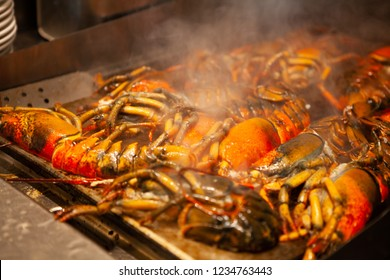 Sizzling hot cooking on the griddle pan. Delicious grilled halved Lobster with butter. Fresh, juicy and tasty Maine Lobster or American lobster. Sweet and flavorful lobster. Rich in omega-3 fatty acid