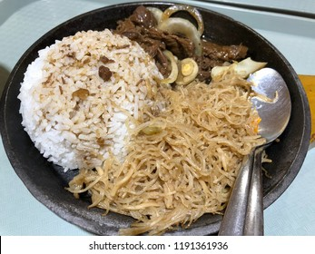 Sizzling platter of steamed rice, beef steak and noodles