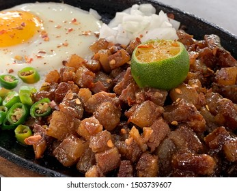 Sizzling spicy pork sisig with egg ang lime. A Filipino dish.