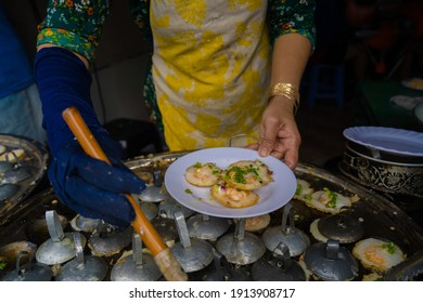 Sizzling Vietnamese mini shrimp pancake and onion- Vietnamese cuisine, Banh Khot. Vendor hawker making Banh Khot