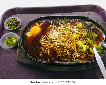Sizzling yee mee noodles hot plate serving with half cook egg, vegetables, mushroom. Delicious food in food court.