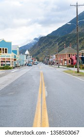 Skagway, Alaska - September 28 2017: Main Street in Skagway looking at shops, parked vehicles and people walking, with autumn color mountains in the background