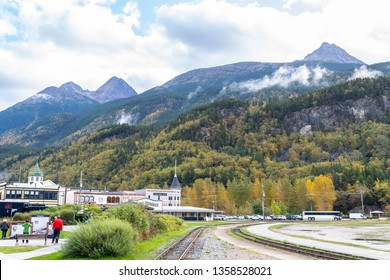 Skagway, Alaska - September 28 2017: Cruise passenger tourists, buildings, train tracks and scenic mountain landscapes in Skagway Alaska
