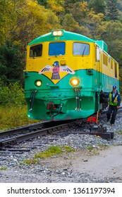 Skagway, Alaska - September 28 2017: White Pass 95 train riding through Skagway towards Yukon on the White Pass & Yukon Route Railway, with conductor hanging on side preparing to dismount/jump off