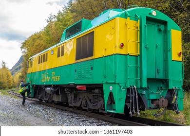 Skagway, Alaska - September 28 2017: White Pass 95 train riding through Skagway towards Yukon on the White Pass & Yukon Route Railway, with conductor climbing aboard