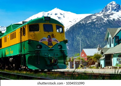 Skagway, Alaska, Us - Circa June 2016: Yellow-green train on the  railroad with snowy mountain hills and street of Skagway in the background by Darko Markovic