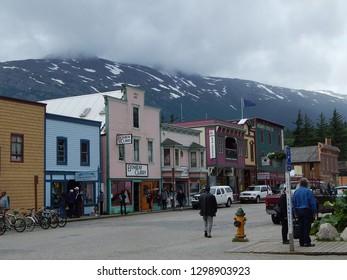 Skagway, Alaska, USA - July 3, 2013: Main Street through downtown Skagway, an Alaskan Gold Rush town, with mountains in the background