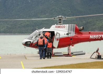 Skagway, Alaska / USA - July 4, 2016: Tourist boarding a helicopter to go on an dog sledding adventure in Denver Glacier
