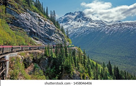 Skagway, Alaska, USA - May 22, 2019 The White Pass & Yukon Route Railroad travels along the rails below Slippery Rock on the way to Skagway.