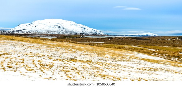 Skalholt, Iceland: Winter landscape of show covered field with a mountain in the backgground.