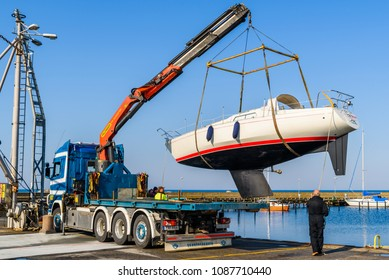 Skanor, Sweden - April 28, 2018: Travel documentary of everyday life and place. The launching of a sailboat using a mobile crane on a truck on a calm and sunny day in spring.