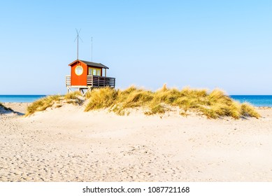 Skanor, Sweden - Lifeguard cabin behind a grassy sand dune on a sunny and clam day.