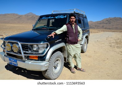 Skardu, Pakistan - October 2, 2016: A Pakistani male driver dressed in Salwar Kameez poses with his Toyota Land Cruiser four wheel drive jeep at northern Gilgit-Baltistan province.
