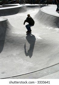 Skate boarder traversing the bowl by himself