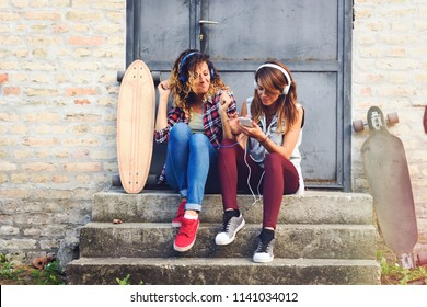 Skate girls sitting in the street hanging out listening music with earphones and smartphone