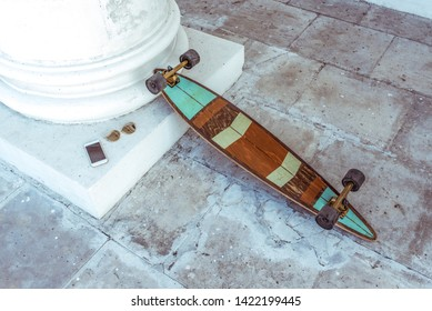 Skateboard board longboard, lies in city in summer at white column, the background is an old tile. Sunglasses in gold right, mobile phone, smartphone. Active lifestyle, fashion style trends.