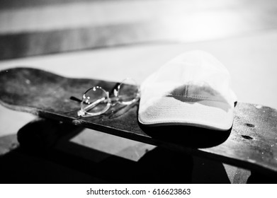Skateboard with glasses and cap on skate park at evening.