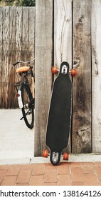 A skateboard longboard stands near a wooden wall. Bike next to the longboard. Background no people. Image
