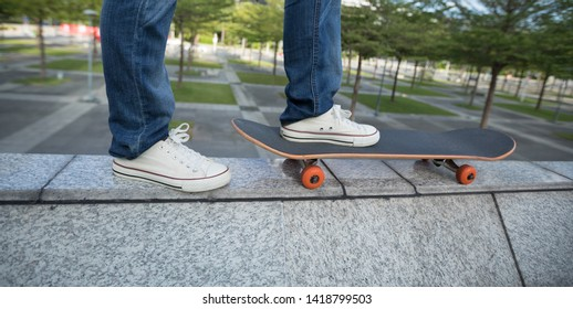 Skateboard on the edge of a urban building wall at city