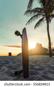 Skateboard and palm tree on Ipanema Beach, Rio De Janeiro. Sunset light behind famous mountains.